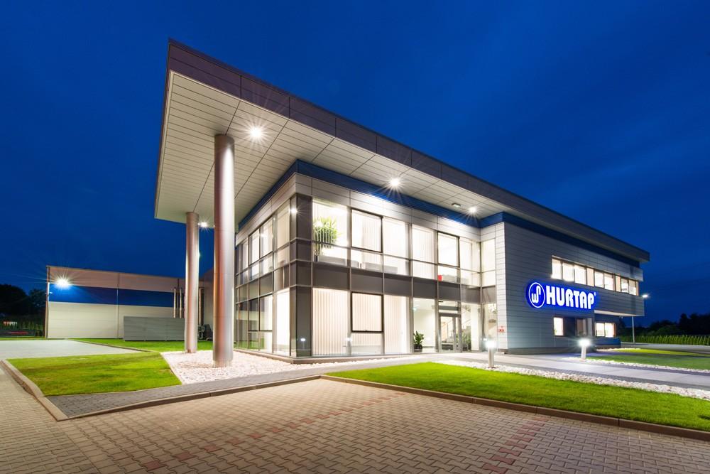 widok budynku nocą - hala magazynowa z budynkiem biurowym, dla Hurtap SA, Głogów, woj. dolnośląskie