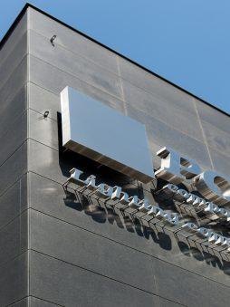 zbliżenie na logo - hala produkcyjno-magazynowa z budynkiem biurowym, dla Polamp, Bieniewiec, woj. mazowieckie