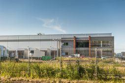 widok zza ogrodzenia - sortownia owoców z częścią biurową, dla Europejskie Centrum Owocowe, Rębowola