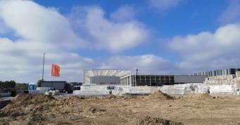 widok na konstrukcje hali mechaników i rozbudowywaną halę - inwestycja dla producenta okien PVC, AdamS, w Mrągowie, woj. warmińsko-mazurskie, budowa CoBouw Polska
