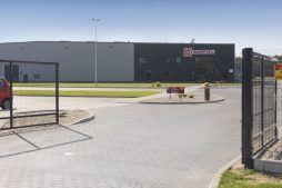 widok ogólny od strony bramy wjazdowej - hala produkcyjna z częścią biurową, dla Dinopol, Ostrów Wlkp.