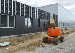 montaż elewacji budynku z okładziną ze spieków kwarcowych i paneli elewacyjnych - hala magazynowa DKS w Kowalach, woj. pomorskie