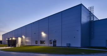 widok na halę produkcyjno-magazynową Kentaur Production - budowa dla duńskiego inwestora, producenta odzieży roboczej, w Łobzie, w woj. zachodniopomorskim, przez generalnego wykonawcę hal, firmę CoBouw Polska