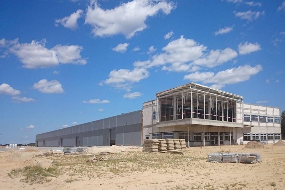 zdjęcie z oddali w trakcie budowy - hala produkcyjno-magazynowa z budynkiem biurowym, dla Lidermax, Łukowo, woj. mazowieckie