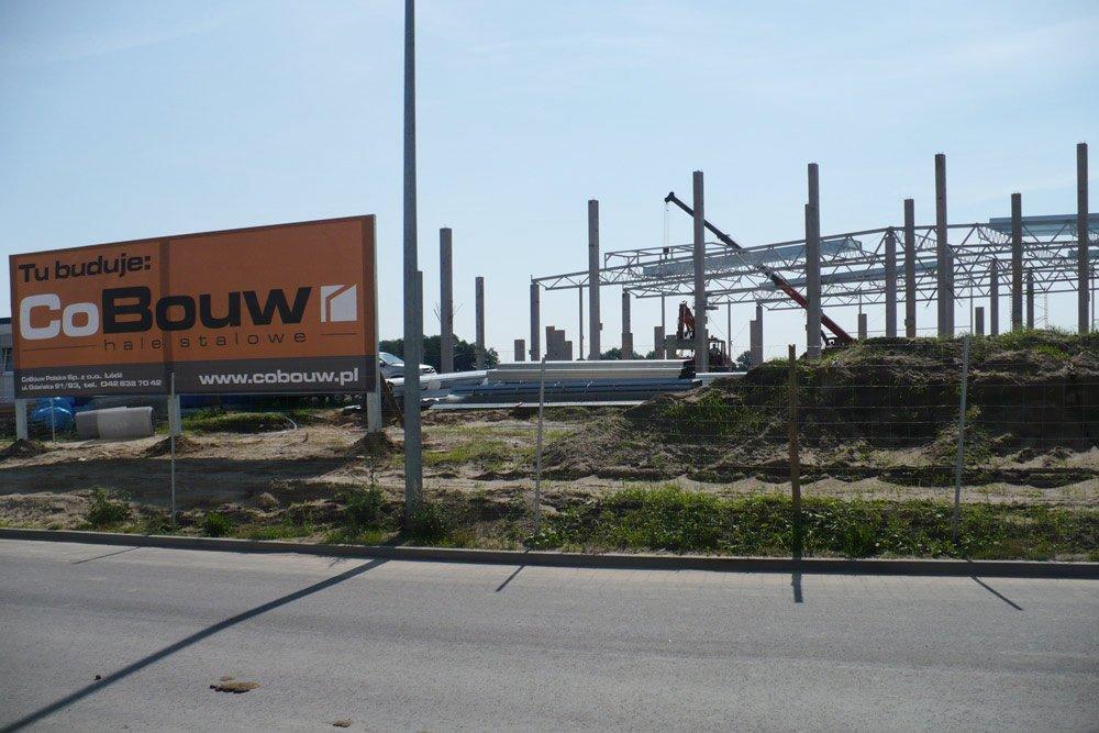 baner reklamowy na tle inwestycji - hala produkcyjna z budynkiem biurowym, dla NWM, Gubin