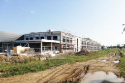 widok na budowę hali producyjno-magazynowej - zakład produkcyjno-magazynowy z częścią socjalno-biurową, dla Linea, Koszlain, woj. zachodniopomorskie