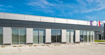widok na część biurową inwestycji - hala produkcyjno-magazynowa wraz z budynkiem socjalno-biurowym, pralnia przemysłowa, dla Bardusch Polska, w Bochni, woj. małopolskie