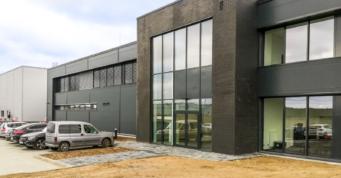 widok obiektu od strony budynku biurowego - hala dla Kentaur Production, producenta odzieży roboczej, z Łobza, w woj. zachodniopomorskim